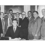 "December 23, 1981 Governor Ed King (seated), signs Mass General Law 150E, which defines members of the Boston Police Detectives Benevolent Society as ""Professional Employees."" Left to right: Attorney Mike Muse, The late Dan Mahoney, First President BPDBS, State Representative Jim Brett, Dorchester, State Representative Tom Finneran, Mattapan, The late Representative Kevin Fitzgerald, Mission Hill, The Late Detective Bob Chennette, Organized Crime, State Representative Michael Flaherty, South Boston, The late Detective Dave Driscoll, District 4, The Late Detective Tom Connolly from area A-1, The late Detective Frank Sheehan, District 4, The late Detective Dick Driscoll, Headquarters, Retired Detective Mal Maloney, E-5, Retired Detective (Former Deputy) Willis Saunders Jr., Vice Control Unit"